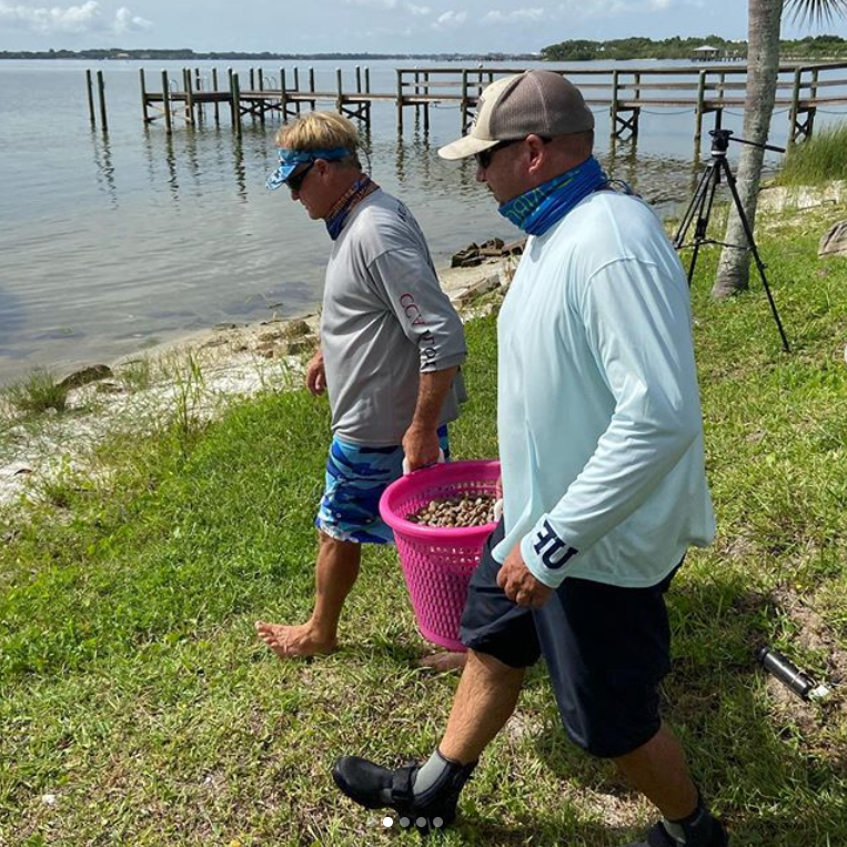 Two men deploying clams into the Indian River Lagoon